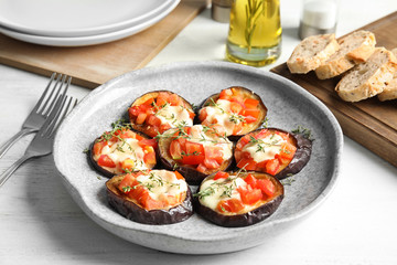 Baked eggplant with tomatoes, cheese and thyme on table