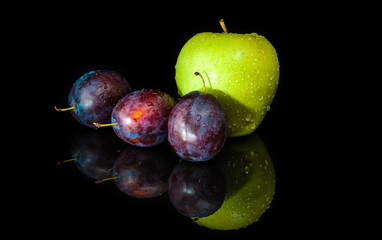 Wet plums and an apple on a mirror