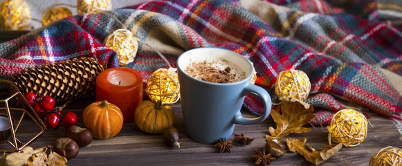Cup of coffee with autumn decorations and cozy scarf