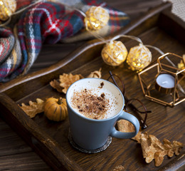 Cup of coffee or hot chocolate in a wooden tray, autumn cosy scarf and decorations