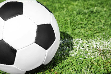 Soccer ball on fresh green football field grass, closeup. Space for text