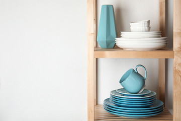 Shelving unit with set of dinnerware on light background, space for text. Interior element
