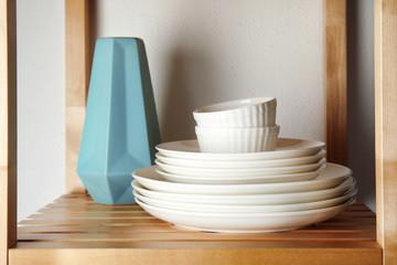 Set of dinnerware on wooden shelf against light background. Interior element
