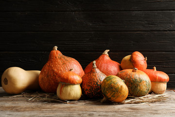 Different pumpkins on table against wooden wall. Autumn holidays