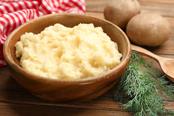 Bowl with tasty mashed potatoes on wooden table