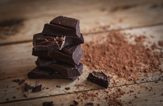 Close-up of stacked dark chocolate on wooden background