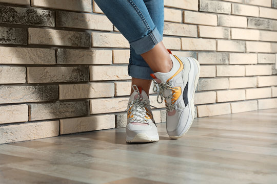 Woman in stylish sneakers near brick wall indoors, closeup