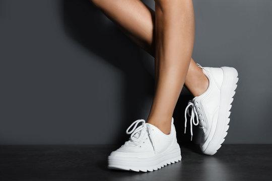 Woman in stylish sneakers near grey wall, closeup