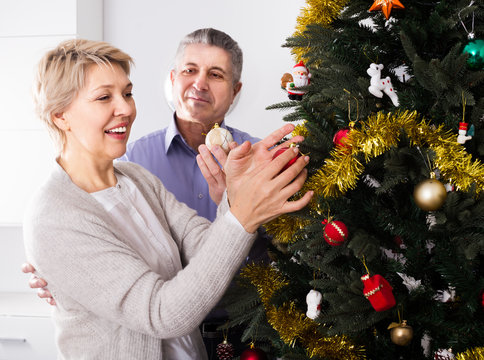 Woman and man 50-55 years old are hang up New Year's toys on a fir-tree