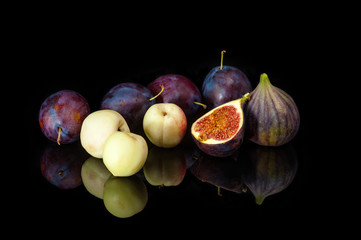 Fresh plums, nectarines and figs on a mirror