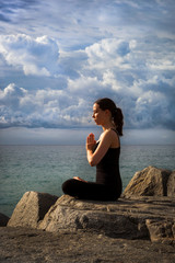 Young woman practicing yoga on rocks at sunrise with dramatic sky