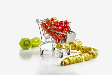Shopping trolley full of tomatoes, pepper on white background