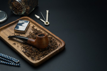 a smoking pipe and a chrome lighter in wooden tray, a pipe tamper tool, pipe cleaners, tobacco jar on the black table
