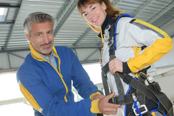 Man attaching harness onto female skydiver