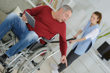 man wheelchair giving orders to carer