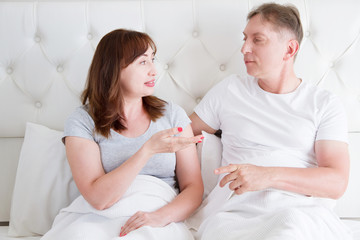 Middle age family couple talking in bed in the morning. Woman and man have dialogue. Healthy relationship. Love and romance