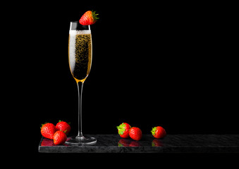 Elegant glass of yellow champagne with strawberry on top and fresh berries on black marble board on black background. Space for text