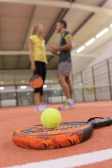 tennis racket and ball in foreground couple in background