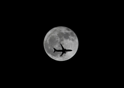 Passenger plane passes the moon as it comes into land at the international airport in Chennai