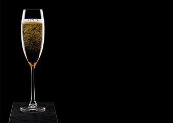 Elegant glass of yellow champagne with bubbles on blavk marble board on black background. Space for text