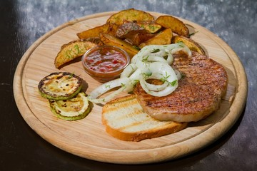 Grilled chicken meat with pickled onions and zucchini, fried potatoes, served on wooden plate, beautiful food photo