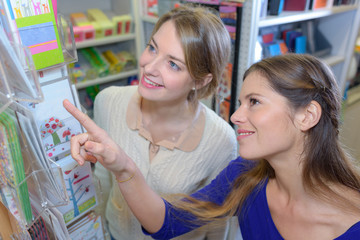 Women looking at greeting cards in store