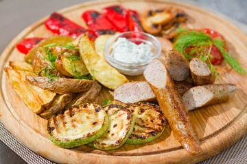 smoked sausages with grilled tomatoes, paprika, mushrooms, zucchini, fried potatoes, dill, white sour sauce, macro shallow dof food photo