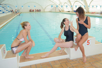 Ladies sat on swimming pool starting blocks
