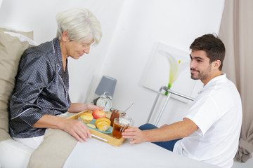 Young man serving breakfast in bed to elderly lady