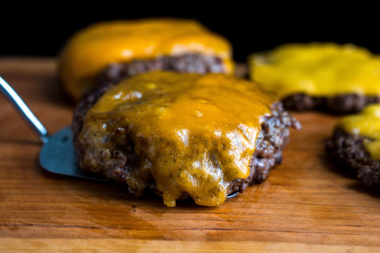 Close up of roasted burger patties on wooden table