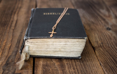 a bible and golden cross on wooden background
