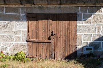 Puerta antiguade madera marrón en cobertizo gallego de muro de piedra