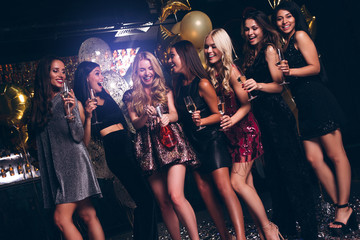 Cheers girls! Beautiful young women in evening gown holding champagne glasses and looking at camera with smile while celebrating in nightclub