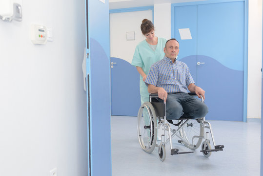 man being pushed in his wheelchair by nurse