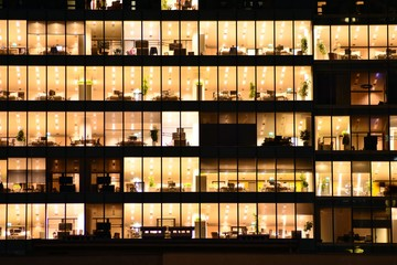 Office building at night. Late night at work. Glass curtain wall office building Fototapete