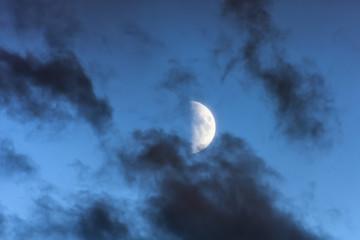 Half moon in the evening in dark clouds.