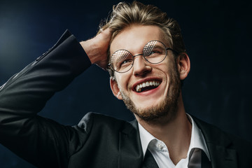 Close up studio portrait of young confident handsome happy smiling man wearing round glasses, white shirt, black jacket, touching his hair, looking up, posing on dark background