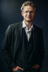 Waist up studio portrait of young confident handsome happy smiling man, businessman wearing round glasses, classic white shirt, black jacket, vest, posing on dark background, looking at camera