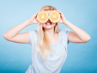 Girl covering her eyes with grapefruits