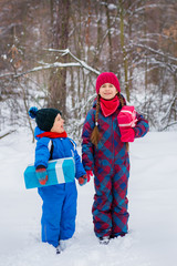 Happy children in a winter snow-covered forest with gift boxes.