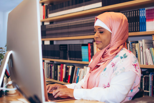 Side view of businesswoman working on laptop in office