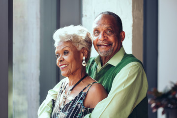 Smiling senior couple standing at home