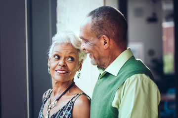 Smiling senior couple looking at each other while standing at home