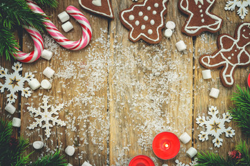 Wood dark background with Christmas tree, candies, cookies, marshmallow and snowflakes