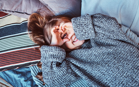 Close-up portrait of a little girl in warm sweater lying on bed.