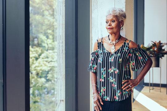 Senior woman looking through window at home