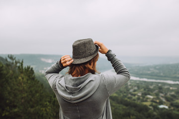 Young man stands with his back and looks at a very beautiful landscape.He holds the hat with both hands