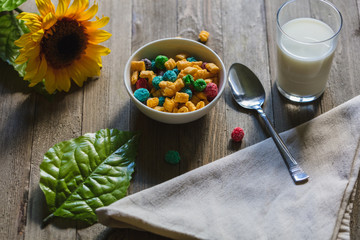 Close up of cereal and sunflower with glass of milk