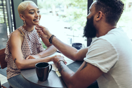 Happy young couple dating with each other in cafe