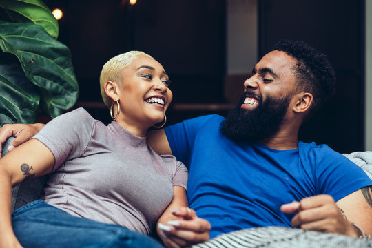 Smiling young couple looking at each other while sitting on sofa